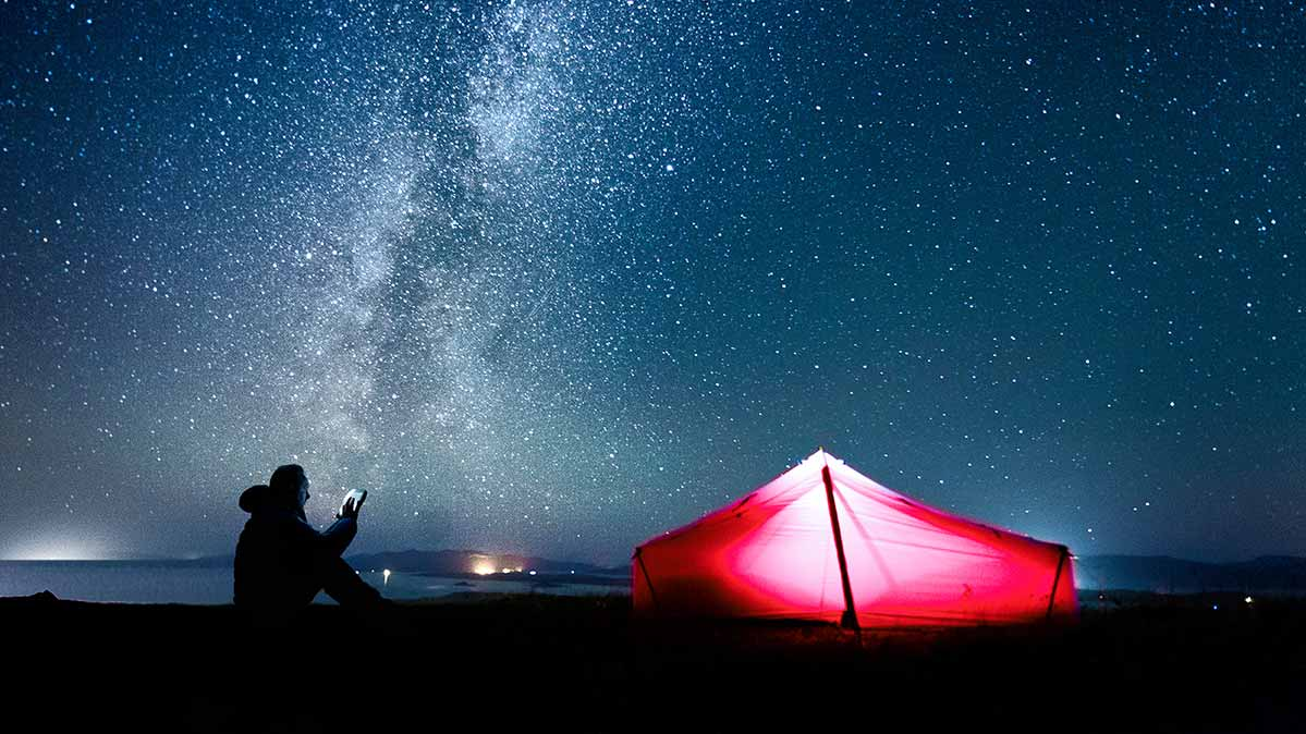 A person camping on a starry night using a smartphone