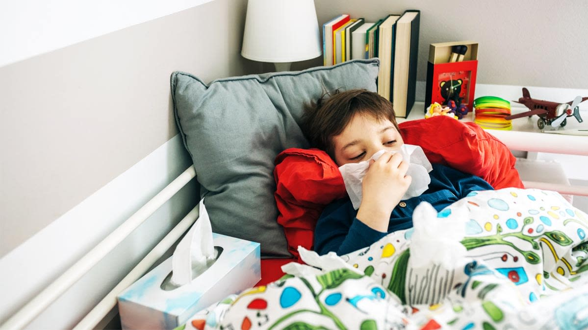 A young boy rests in bed with a box of tissues and holds a tissue to his nose.