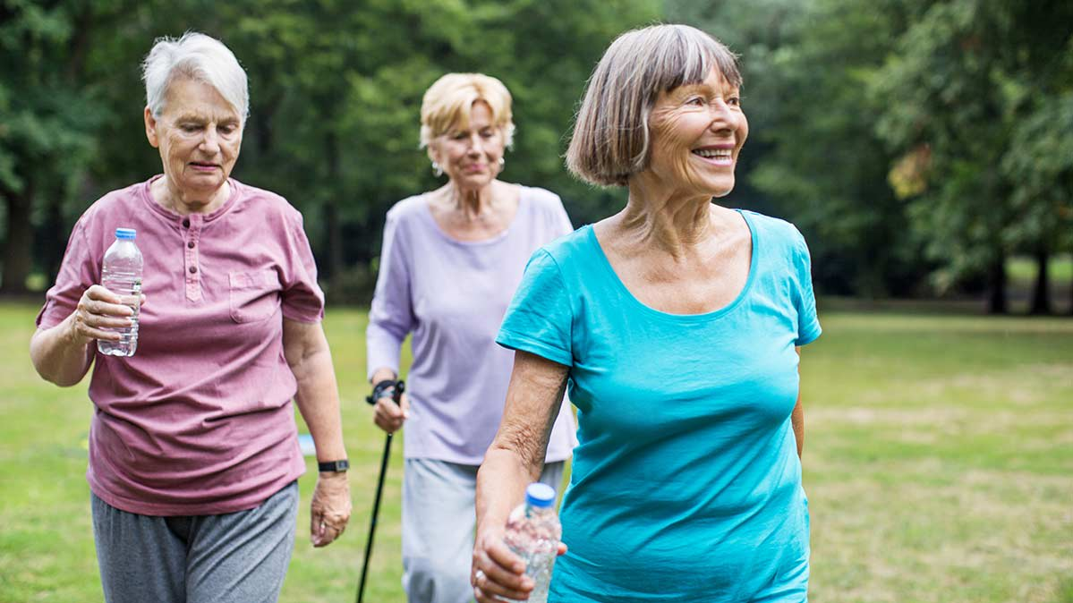 Three senior women walking across a field