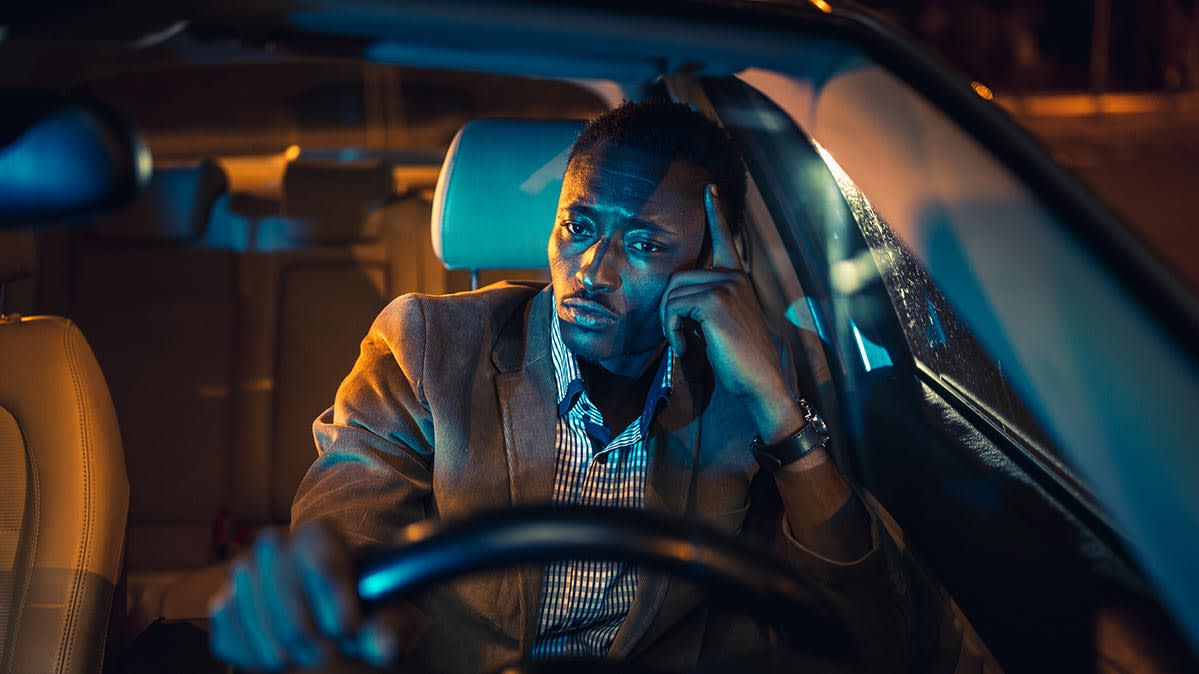 A man sits in the driver's seat of a car at night.