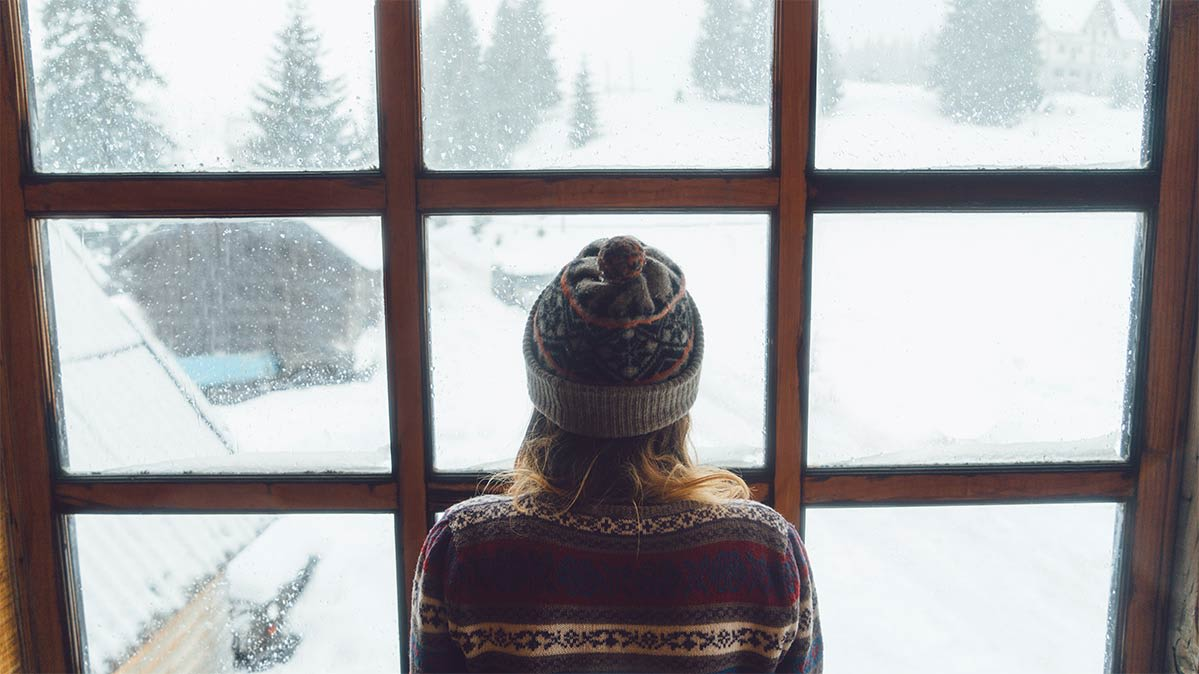 Woman wearing a hat looking out of window onto snowy landscape.