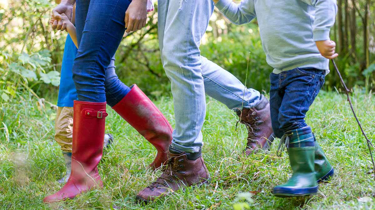 A photograph of hikers' legs, dressed in blue jeans and boots.