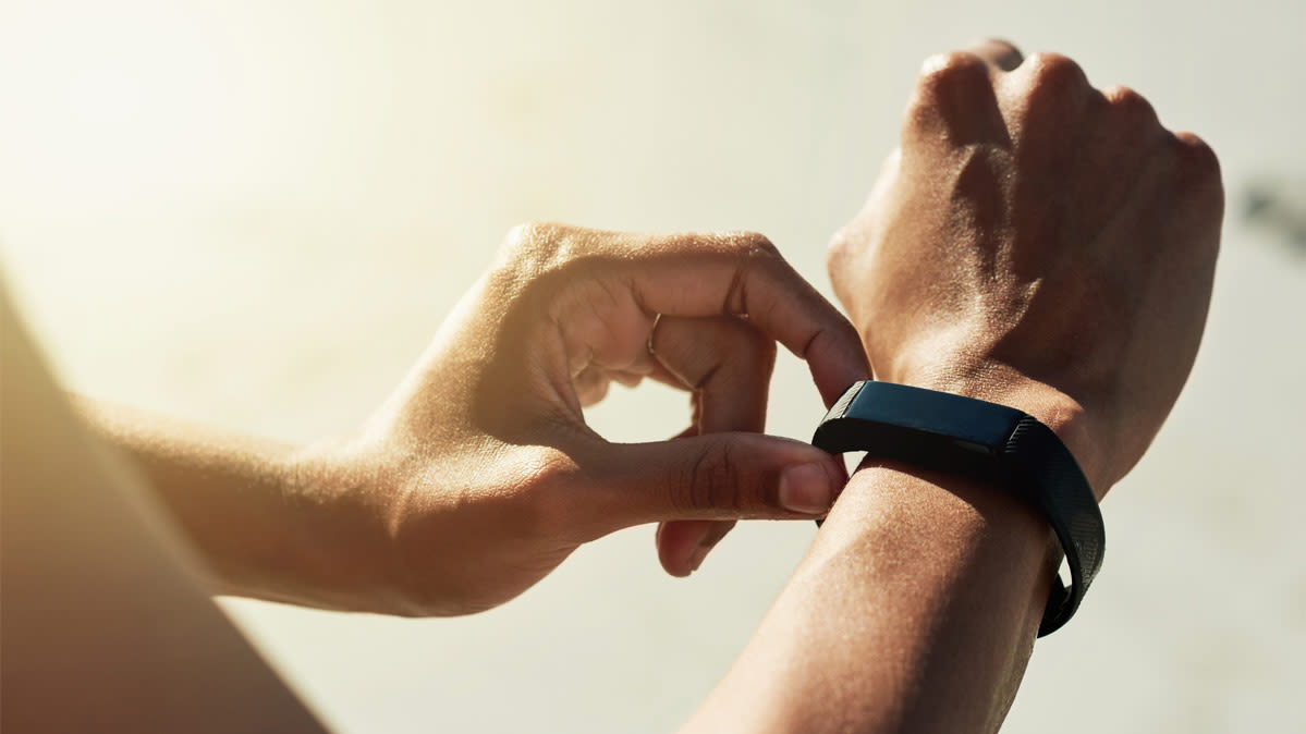 A person touching a fitness tracker on their wrist.