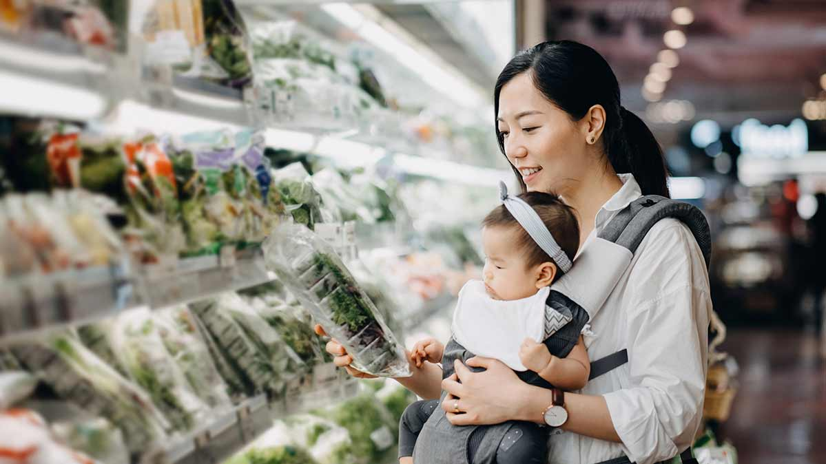 A shopper with a baby in a carrier checking to see if produce is really organic.