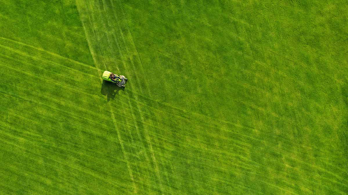 Someone drives a riding mower across a lawn