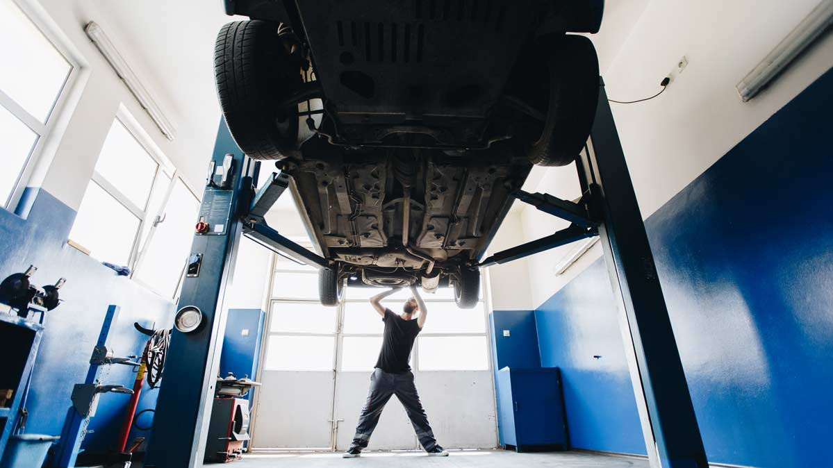 A mechanic inspecting the undercarriage of a car on a lift.