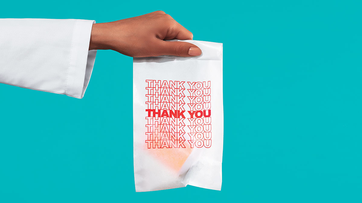 A pharmacist with a 'thank you' bag in hand.