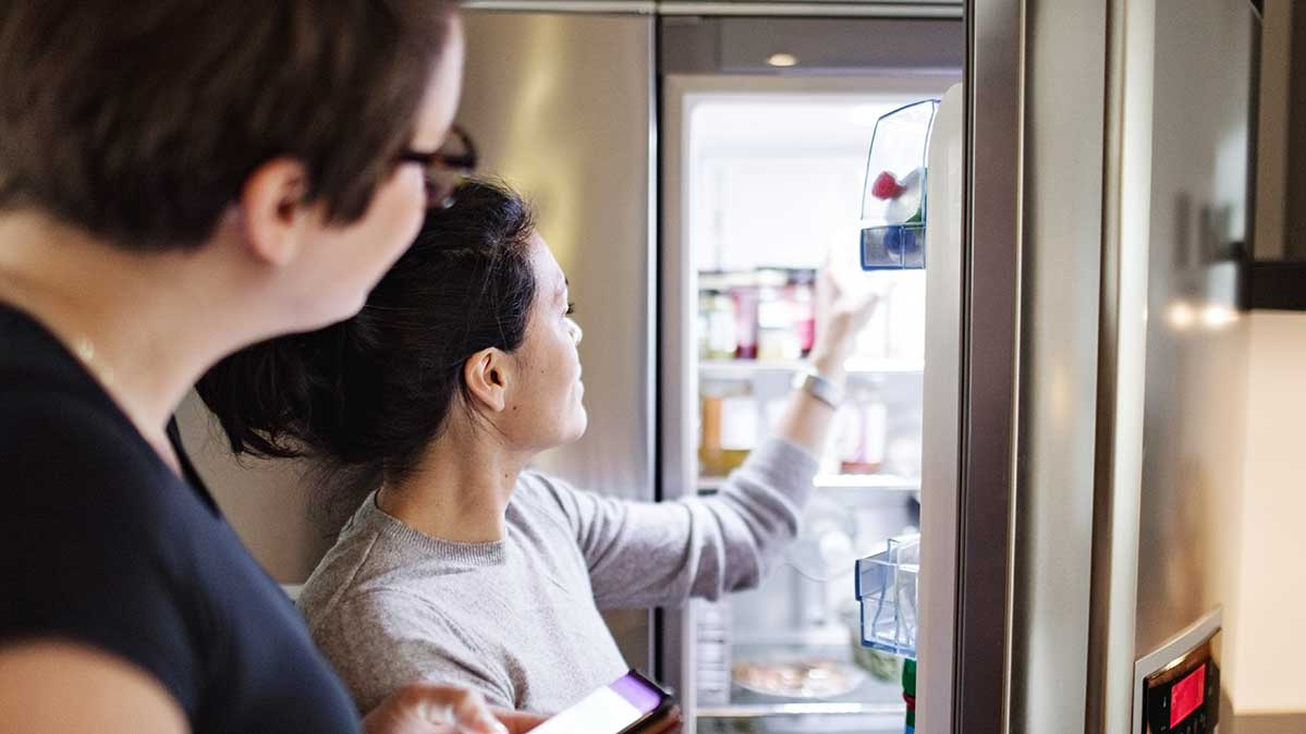 Women looking in a refrigerator