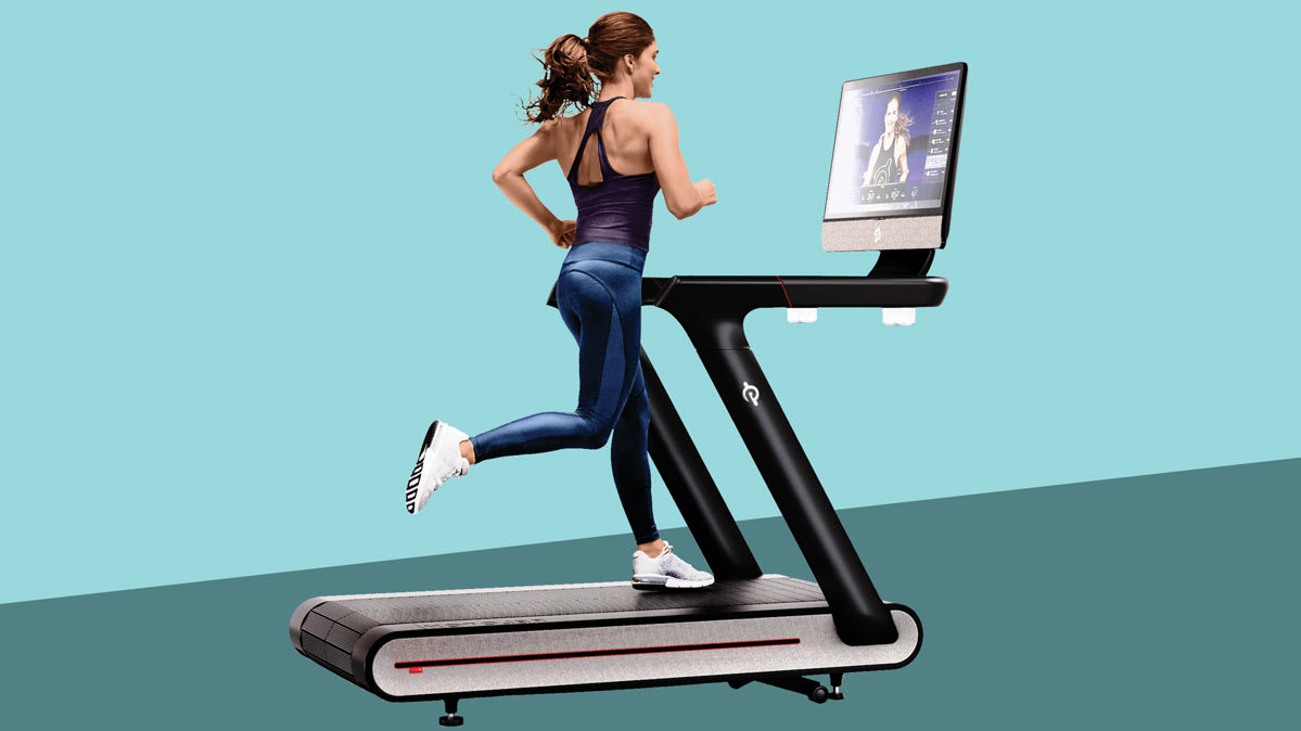 A woman runs on a Peloton treadmill with a screen