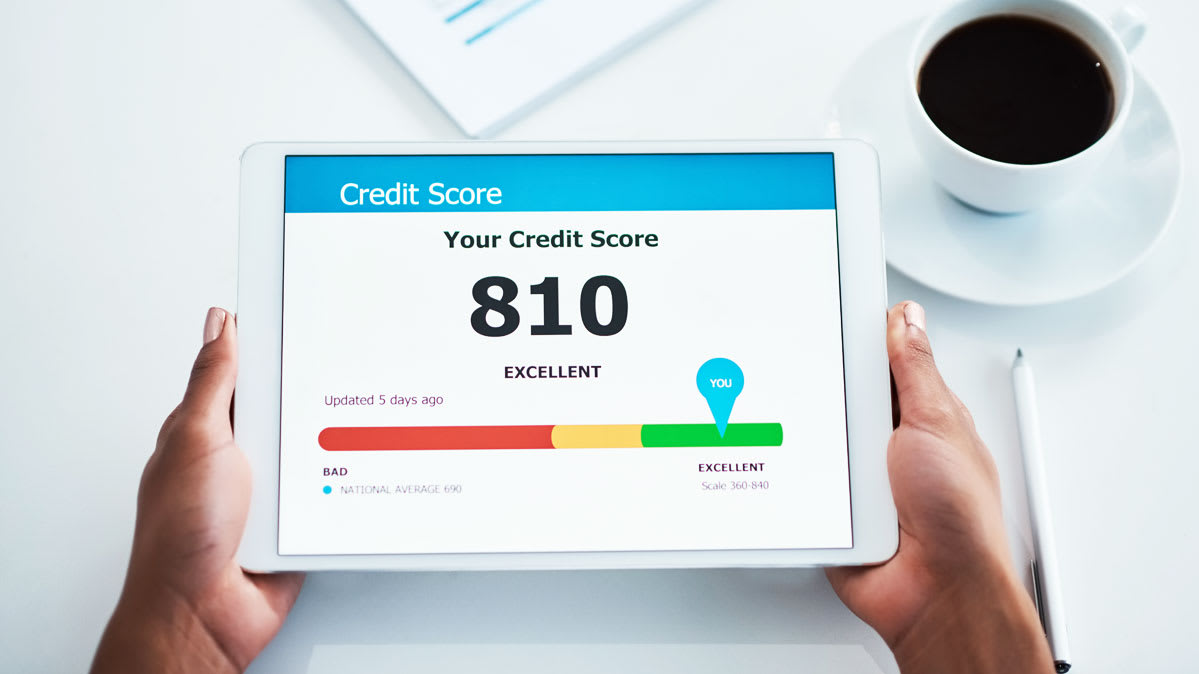 A person holding a tablet with a credit score displayed