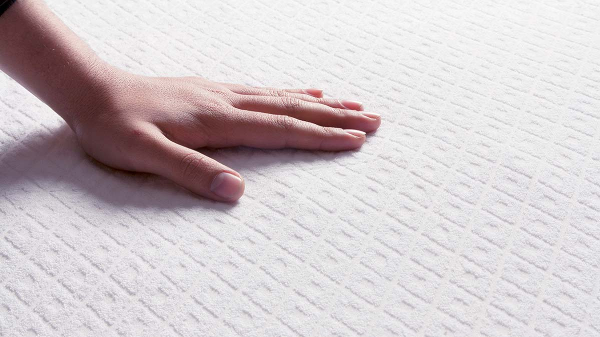 A woman's hand felling the top of a mattress