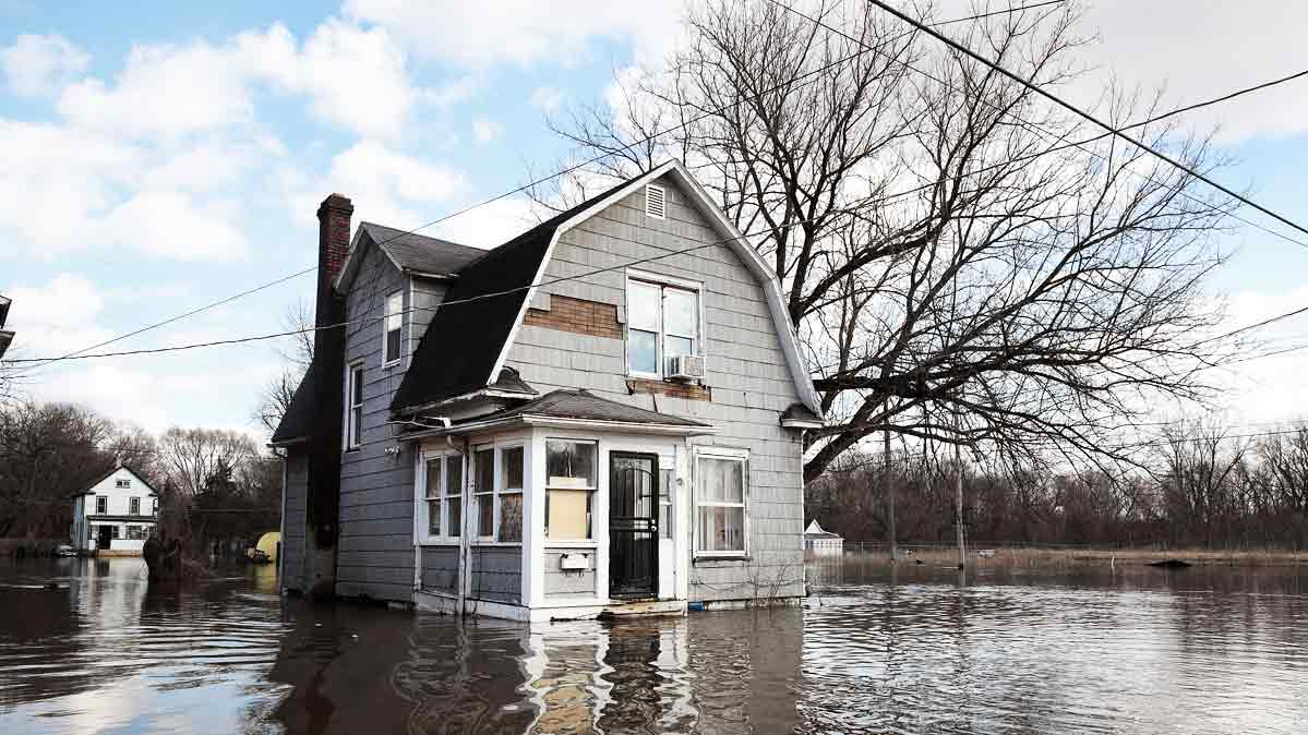 People look at a flooded home after a storm.