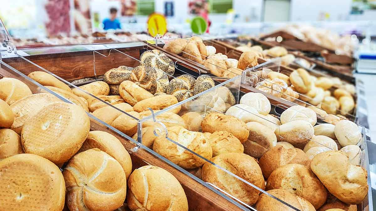 Various bread and rolls on display in a store bakery.