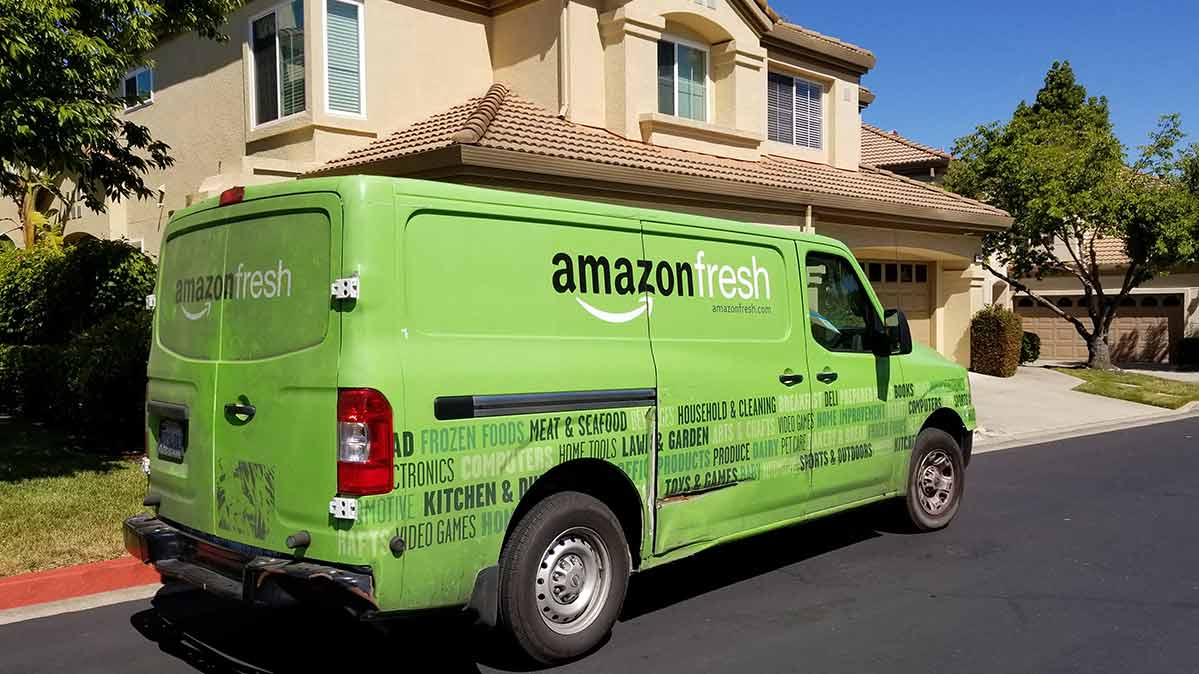 An AmazonFresh delivery truck in front of a house