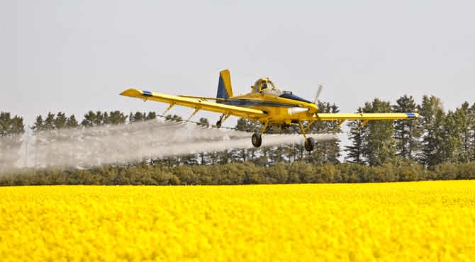 An image of a crop-dusting airplane spraying chemicals over a field.