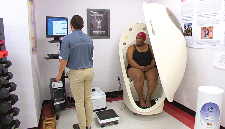 A woman sits in a BodPod as a tester prepares to measure her body fat. It is more accurate than a body-fat scale.