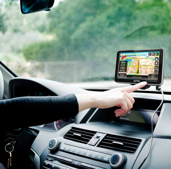 Photo of a person using a portable GPS system in their car.