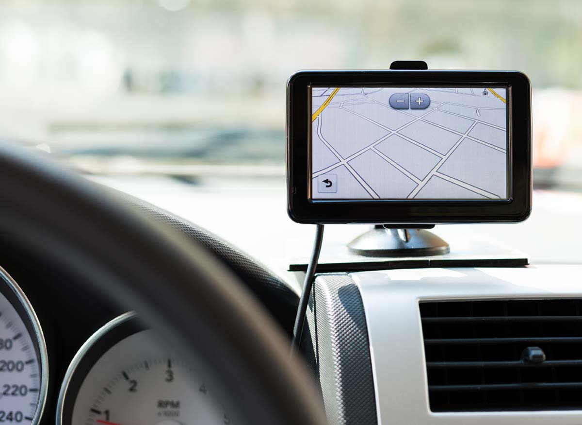 Photo of a GPS mounted on a car dashboard using mounting hardware.