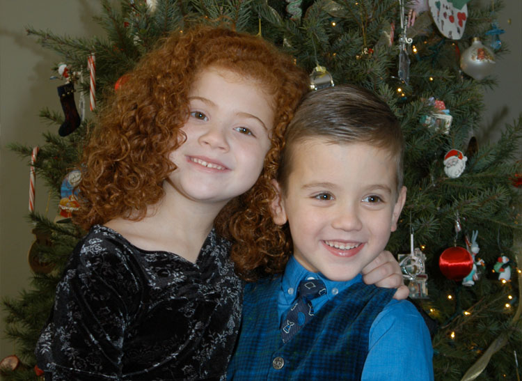 Great holiday photos include an image of two kids by a christmas tree.