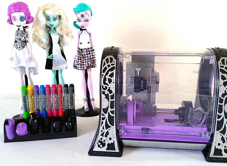A picture of three dolls, nine markers, and the Monster High MonsterMaker