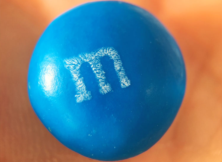 This is a macro photo of a blue M&M candy.