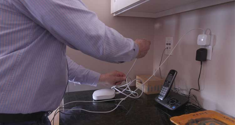 Photo of an Eero Wi-Fi router being lugged into a kitchen Ethernet jack.