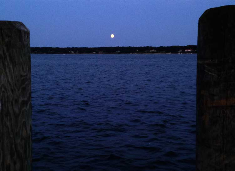This is a photo of the moon over a Long Island bay