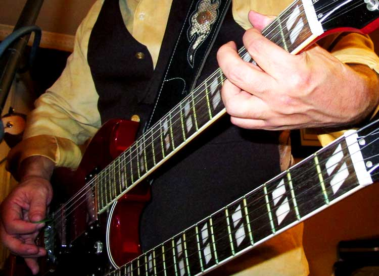 A musician playing a double-neck guitar, another image that illustrates the art of concert photography