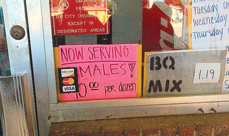 A photo of a restaurant's front window with a sign for tamales partially blocked so it reads as if it serves males $10 for a dozen.