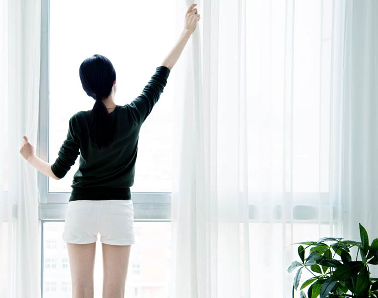 Photo of a woman opening the curtains to a large set of windows.