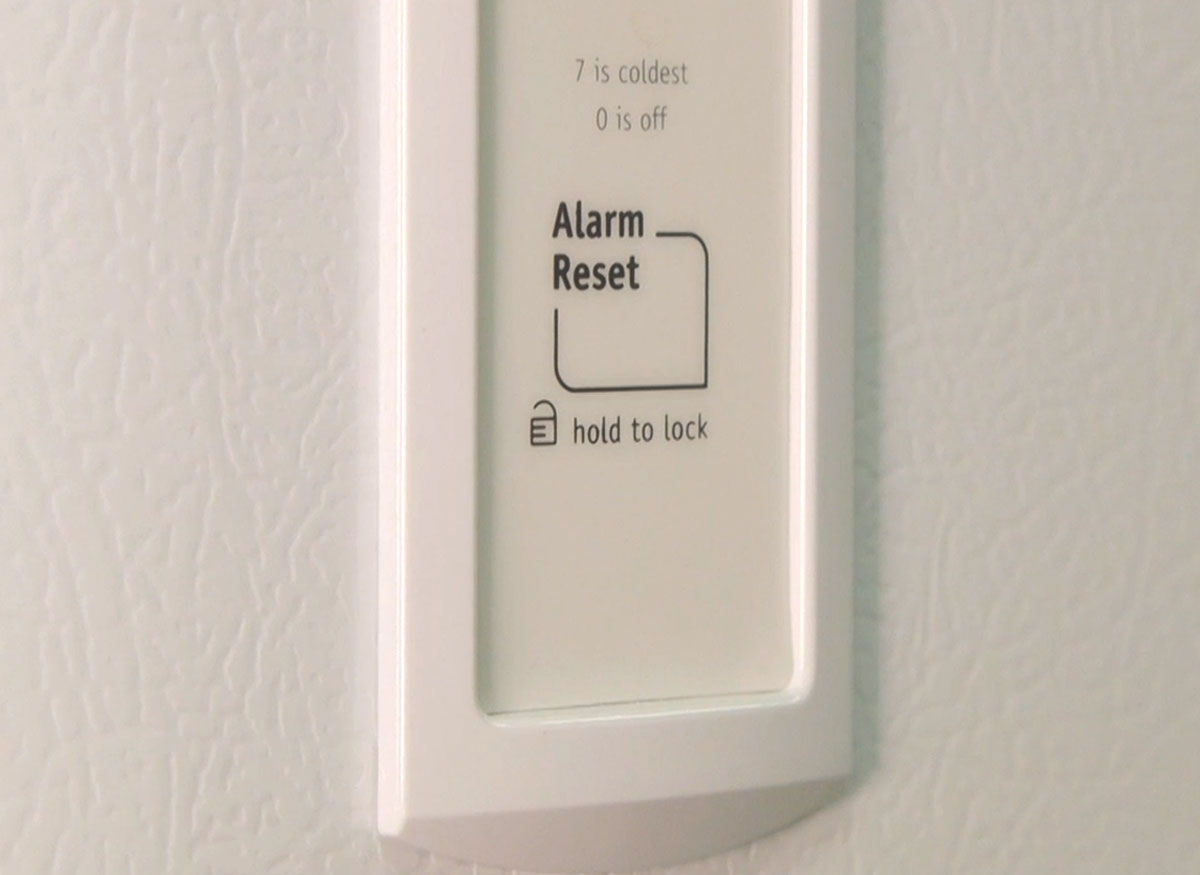 Photo of an alarm reset button on a freezer.