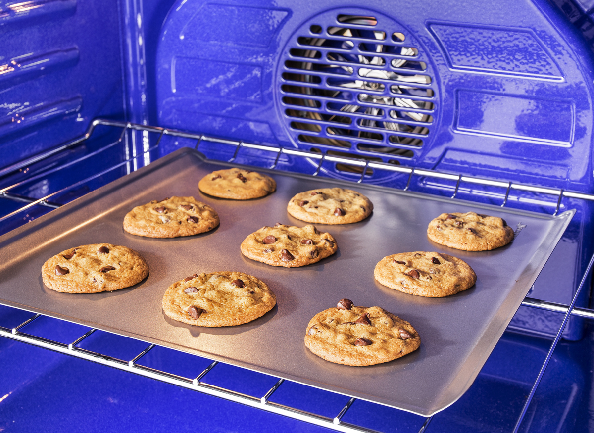 Picture taken inside an oven of a convection heating element in use as someone bakes chocolate chip cookies.
