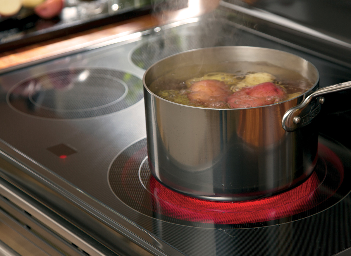 Picture of a hot-surface warning light on a kitchen range that is red as someone boils potatoes in a pot.