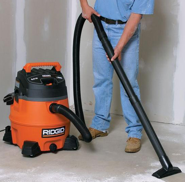 Photo of a man using a medium-sized wet/dry vacuum to clean the floor.