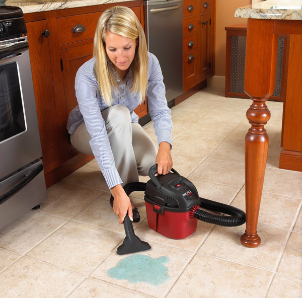 Photo of a woman using a mini-sized wet/dry vacuum to clean up a spill in the kitchen.