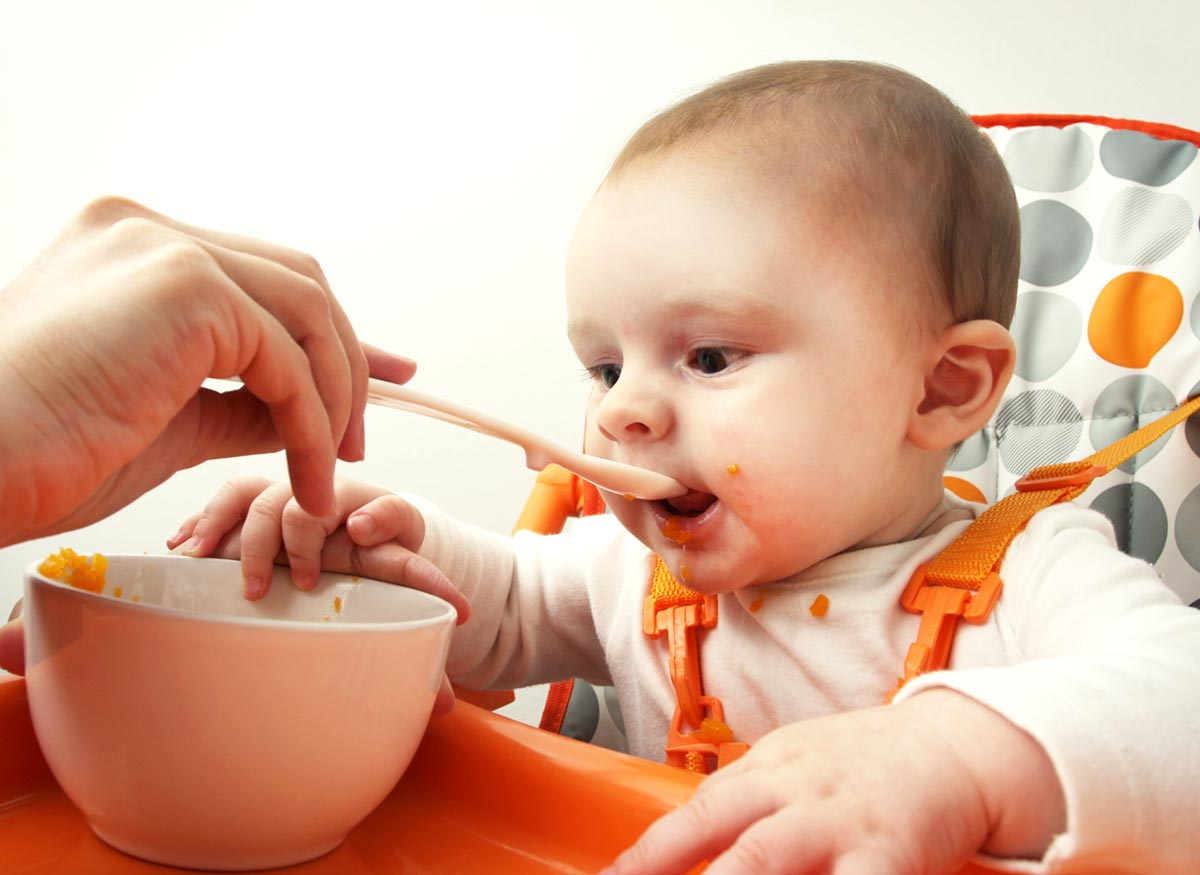 Photo of a baby who is strapped into a safety harness while being fed from a bowl.
