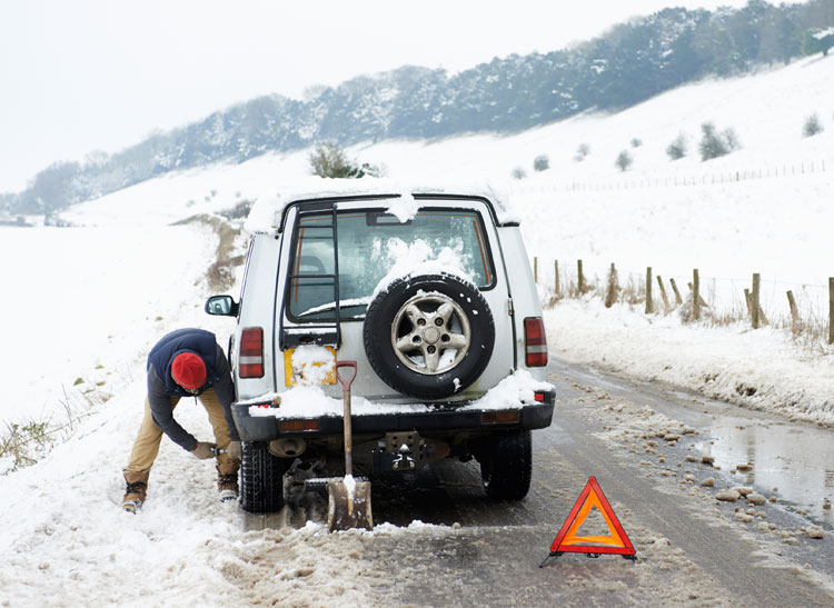 An image of a driver alongside his stalled vehicle on a snowy roadside
