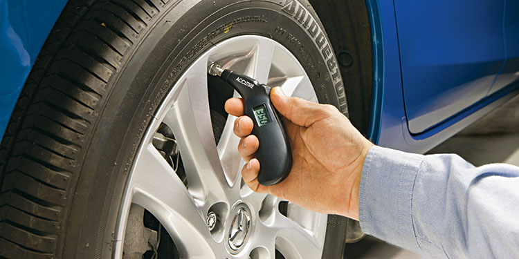 A man uses a handheld tire pressure gauge to check the pressure of one of his front car tires.