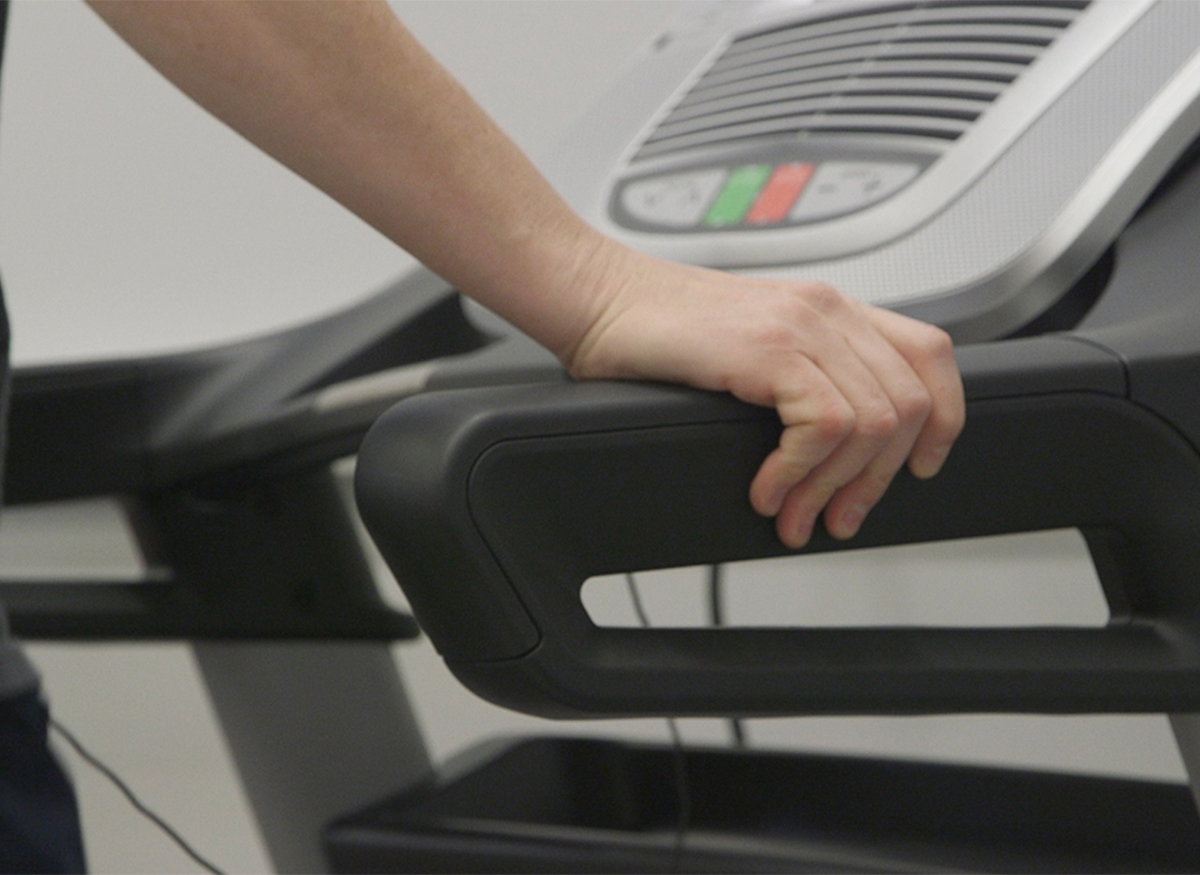 a person using the hand rails on a treadmill.