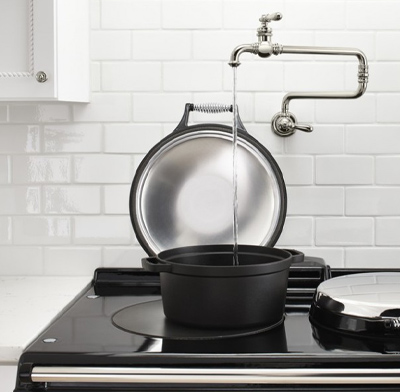Photo of a pot-filler faucet installed above a kitchen stovetop.