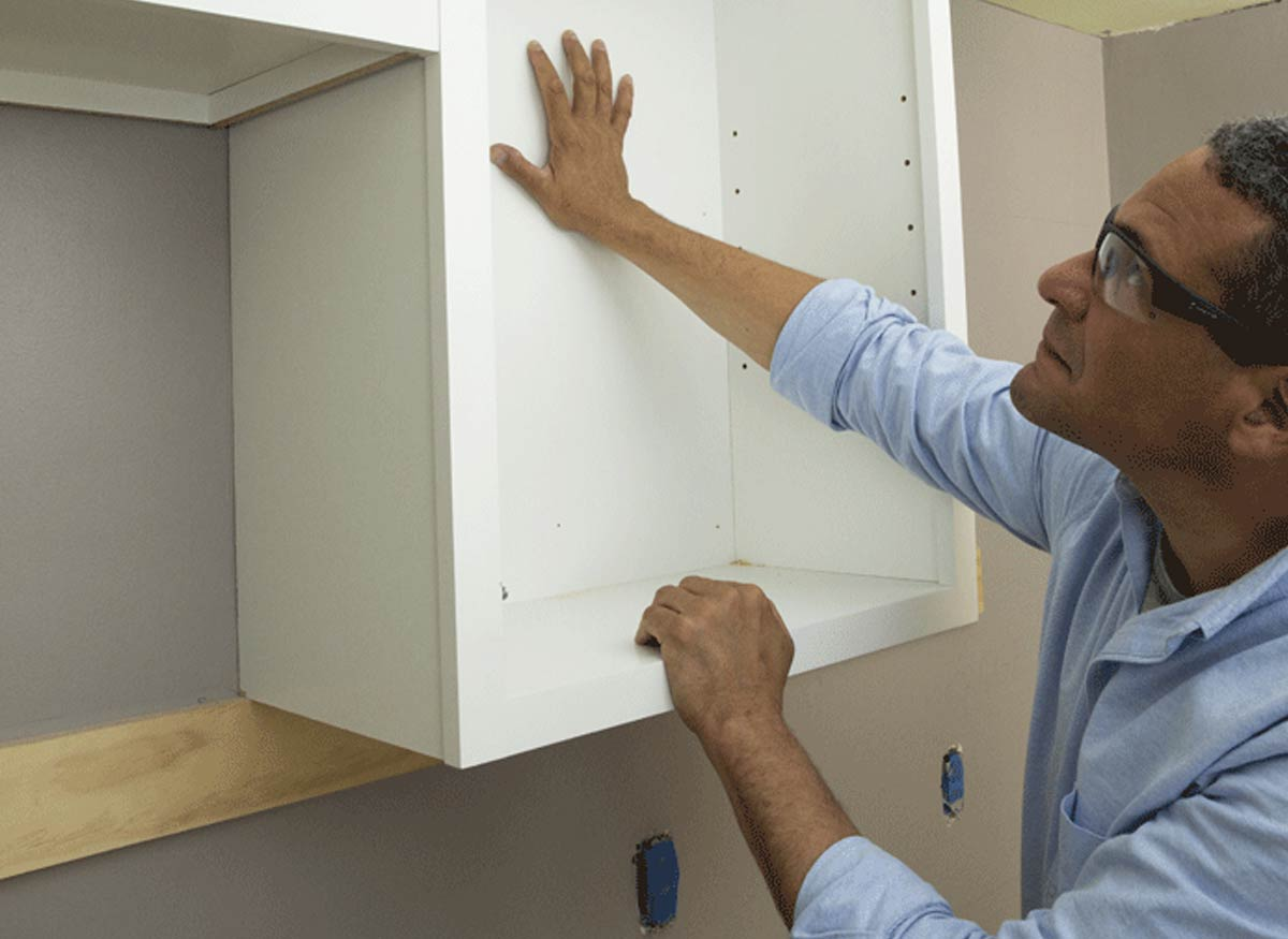Photo of a man installing kitchen cabinets.