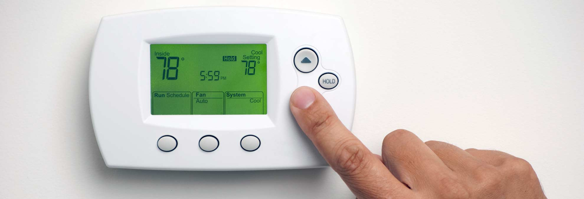 Someone setting the thermostat as part of Consumer Reports' top Appliance stories of the year