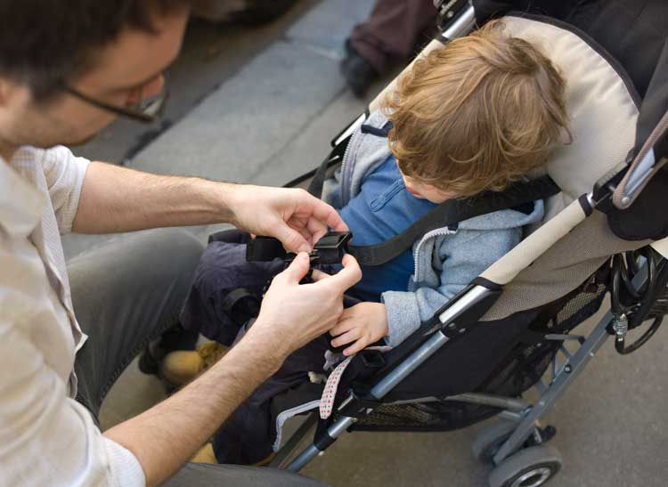 Father buckling a child into a baby stroller.