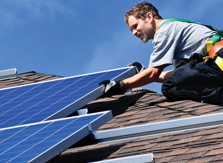 A solar installer attaching a panel to a roof.