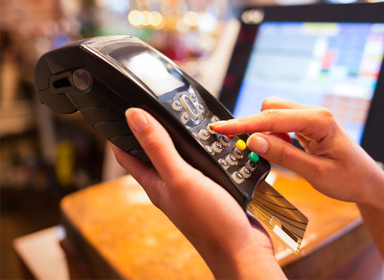 Using an EMV credit card at checkout. New credit card technology rules begin in October.