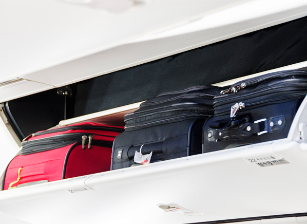 Photo of carry-on luggage in an overhead compartment on a plane.