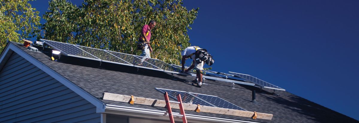 Solar Installers Attaching Solar Panels To A Roof