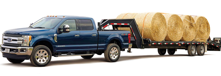 A Heavy Duty Ford Pickup Truck Towing Large Bales Of Hay