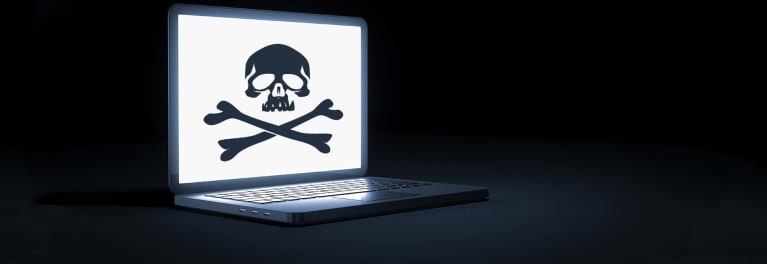 Laptop showing skull and crossbones for article on how to protect yourself against ransomware
