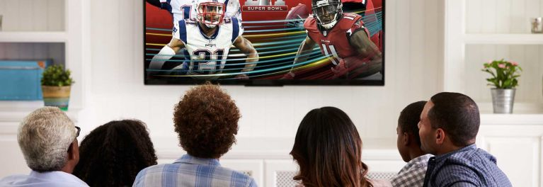 Photo of someone using a remote control and watching a football game on a best TV.